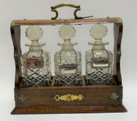 An oak brass bound three-section tantalus enclosing three square section spirit bottles with