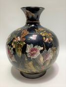A Victorian Royal Doulton faience ovoid flared neck vase, foliate painted upon a dark blue ground,