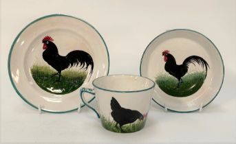 A Wemyss ware black cockerel decorated trio, impressed and printed marks and retailed for T. Goode &