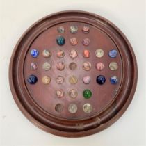A turned mahogany solitaire board with thirty one marbles, diameter of board 35cm.