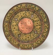 An Indian copper, brass and silver applied dish, decorated in relief with dancing females, the rim