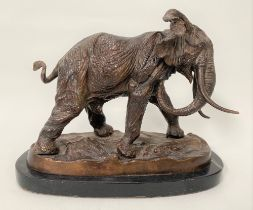 A modern bronze sculpture of a bull elephant upon a naturalistic oval base and with black marble