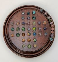 A 19th century mahogany turned solitaire board with forty three glass marbles, diameter of board