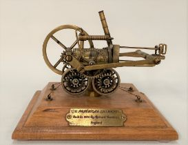 A modern brass scale model of Richard Trevithick's steam locomotive, a brass plaque to the wooden