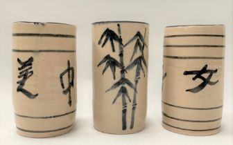 A set of three Japanese pottery brush pots, two with calligraphy inscriptions, the other decorated