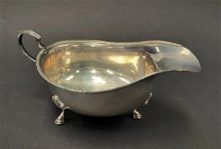 A George V silver sauce boat with beaded rim raised on triple outswept feet, maker T & J.P.,