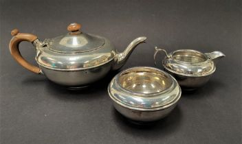 A George V silver three piece batchelor tea set by Charles and Richard Comyns, comprising a squat