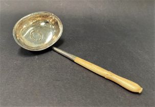 A Georgian white metal toddy ladle, with short carved ivory handle, the oval bowl set with a