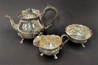 A George V silver three piece batchelor tea set, of ovoid wrythen fluted design, raised on triple