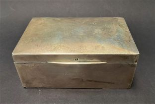 A silver rectangular hinge lidded cigarette box, width 14cm (hallmarks rubbed), weight overall 12.