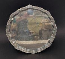 A modern silver salver with pie crust rim by Viners Ltd, raised on triple shell feet, Sheffield
