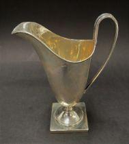 A George VI silver cream jug upon square pedestal base, maker E.V., Sheffield 1938, height 14cm,