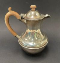 A George VI silver baluster hot water jug with fruitwood handle and finial by Richard Comyns, London