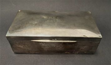 A silver hinge lidded cigarette box, the lid with engraved dedication, width 18cm (hallmarks