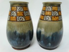 A pair of Royal Doulton stoneware ovoid vases with incised band on a green and blue mottled ground