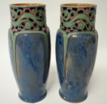 A pair of Royal Doulton stoneware vases with tubeline decoration upon a mottled blue ground, No.