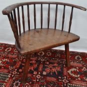 An 18th century bow back chair in elm and ash with thirteen spindle back, lacking one spindle,