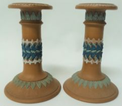 A pair of Doulton Silicone earthenware candlesticks with sprigged decoration, height 15cm.