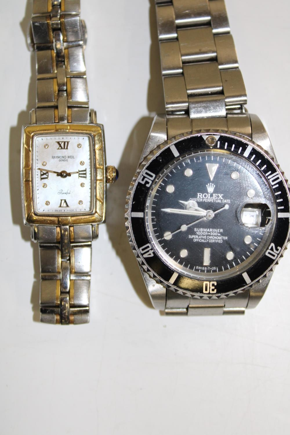 A Raymond Weil watch in GWO and one other