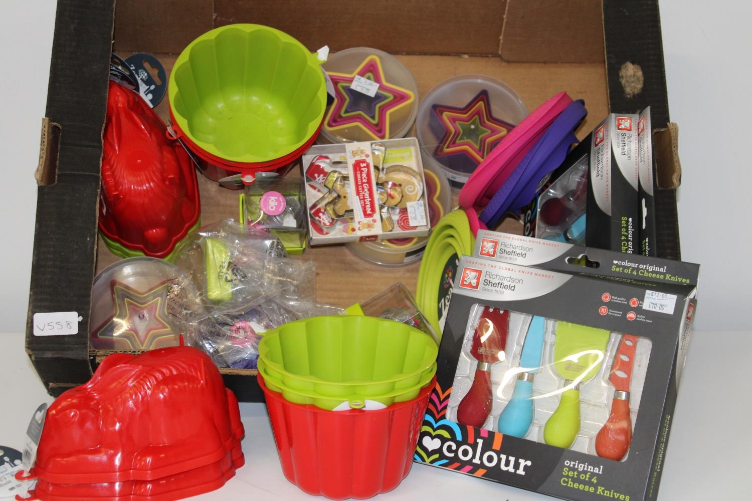 A box of brand new kitchen items, jelly moulds and cutters etc