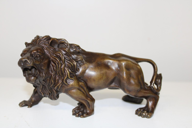 A bronze lion figure 25cm x 9cm