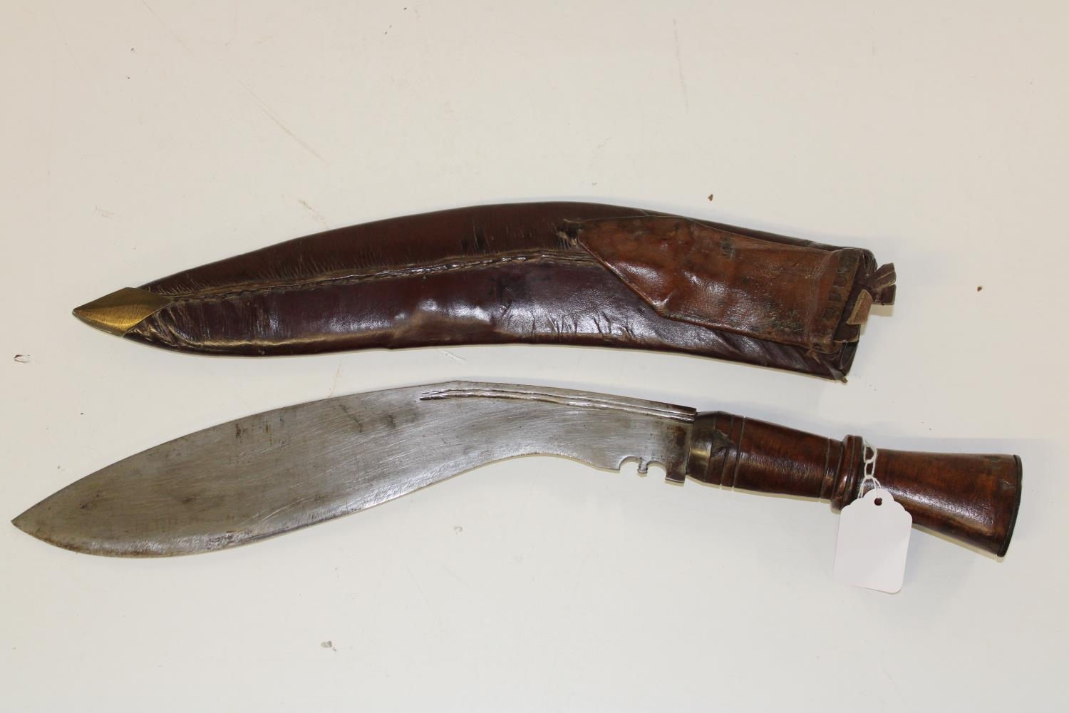 A large Kukri Gurka style knife with a wooden handle in a leather sheath Length of knife 46cm
