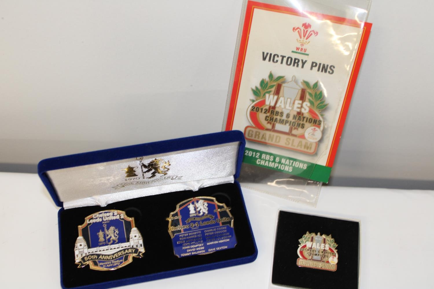 Three assorted sporting related badges