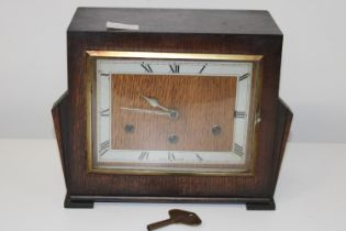 An Art Deco period wooden cased mantle clock with key. (needs attention)