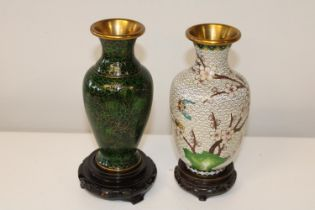 Two Oriental cloisonne vases on wooden stands. 18cm h