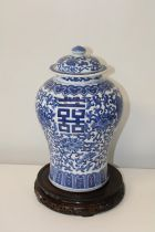 A large Chinese blue & white ginger jar with lid, on a wooden stand. 33 cm h