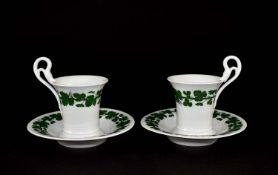 Zwei Tassen mit Untertassen. Klassizistische Form mit Schlangenhenkel. Dazu kleine Vase.