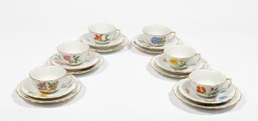 Sechs Teegedecke. Teetassen mit Untertassen und Kuchentellern. Polychrome Blütenmalerei mit
