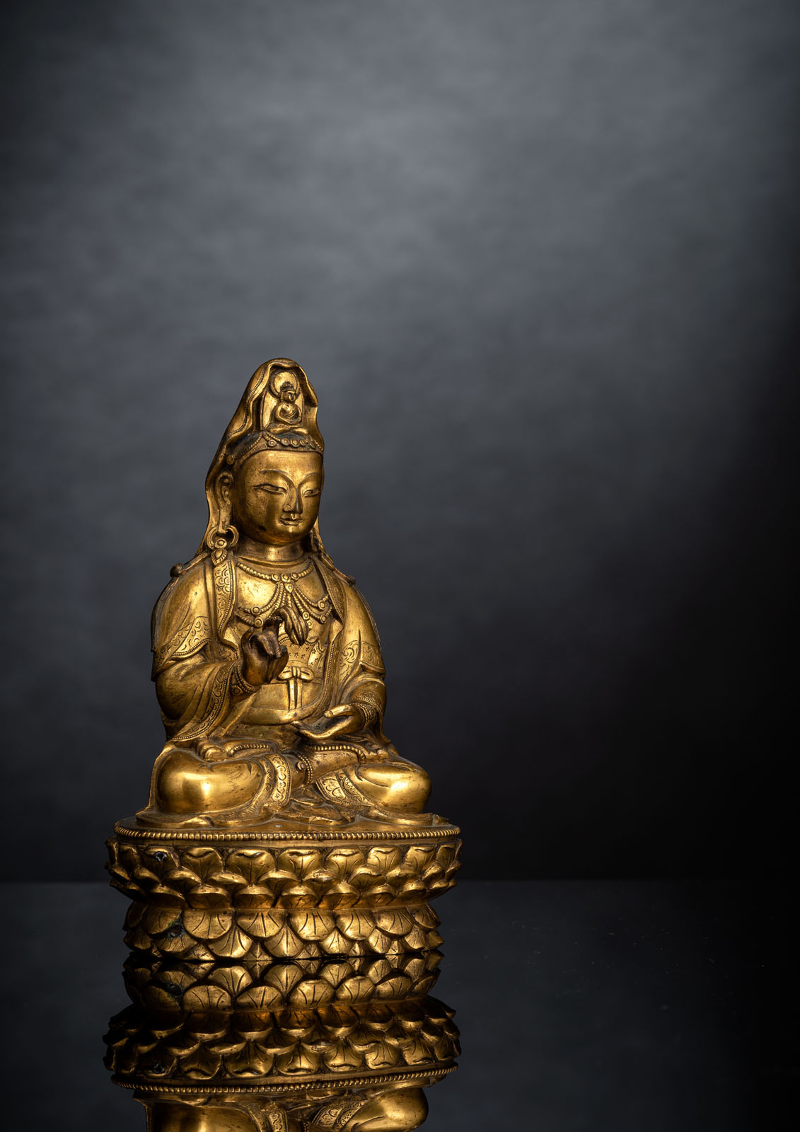 A FINE GILT-BRONZE FIGURE OF GUANYIN ON A LOTOS ABOVE A CARVED HARDWOOD LOTOS STAND - Image 2 of 4