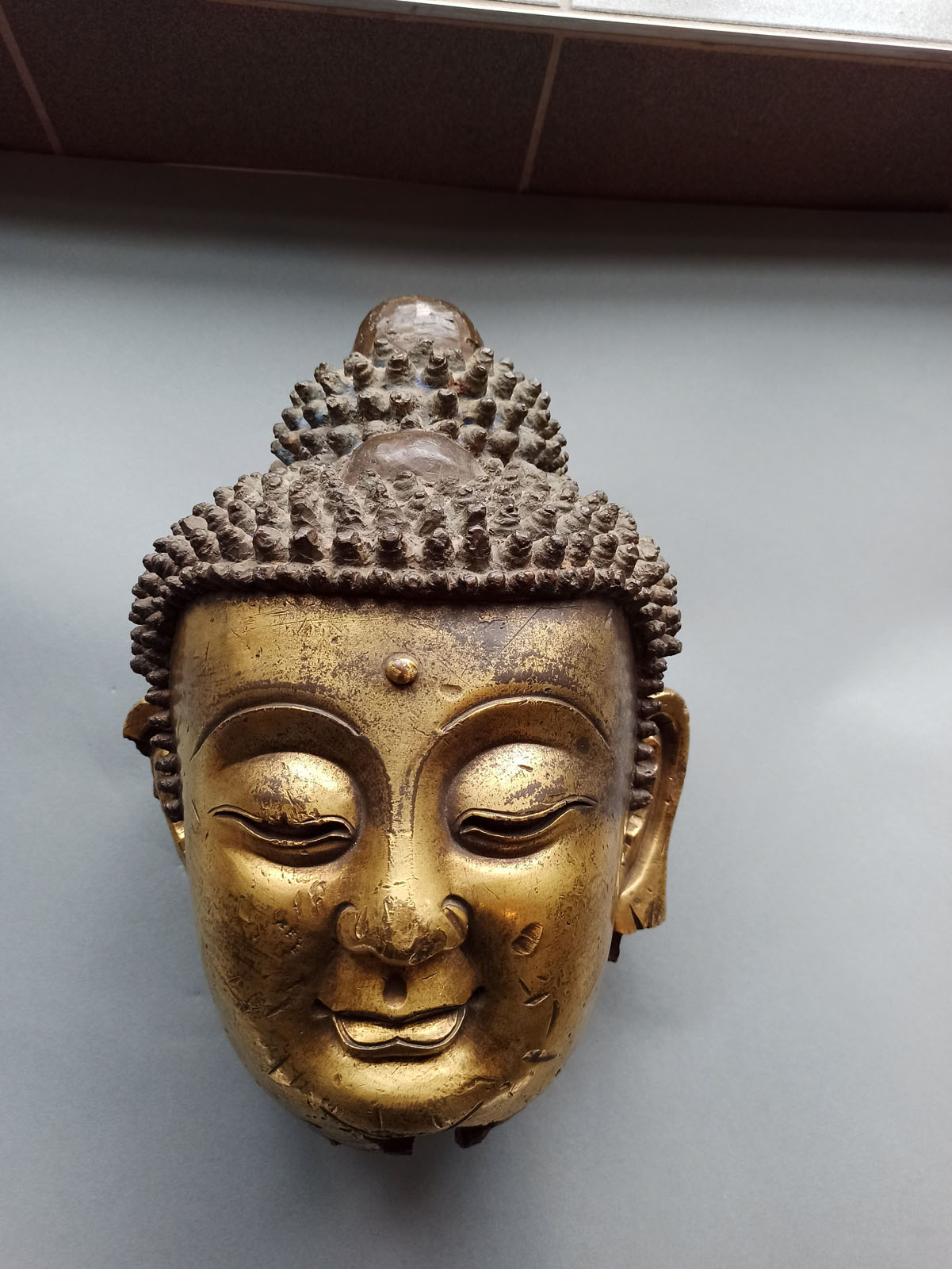 A LARGE GILT-BRONZE HEAD OF BUDDHA ON A WOOD STAND - Image 6 of 13