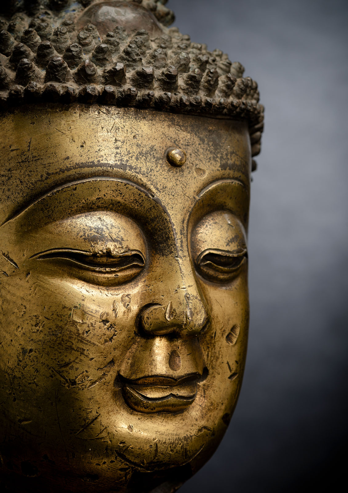 A LARGE GILT-BRONZE HEAD OF BUDDHA ON A WOOD STAND - Image 3 of 13