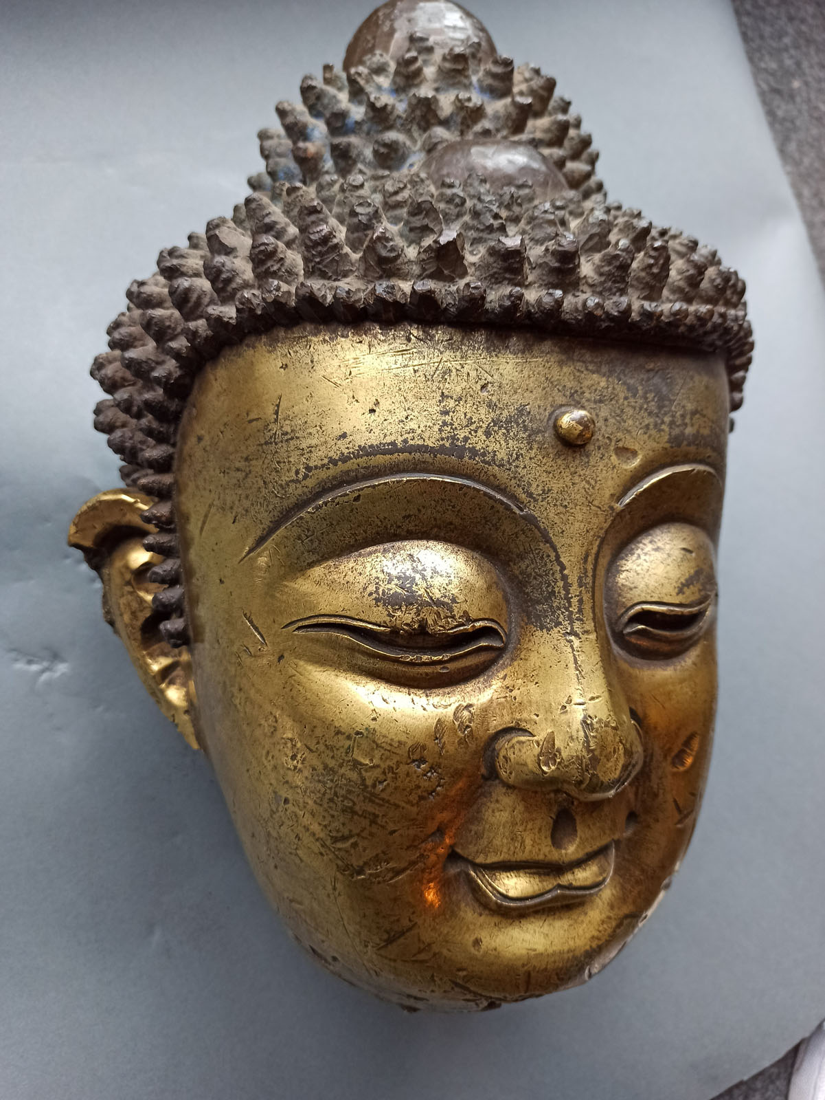 A LARGE GILT-BRONZE HEAD OF BUDDHA ON A WOOD STAND - Image 11 of 13