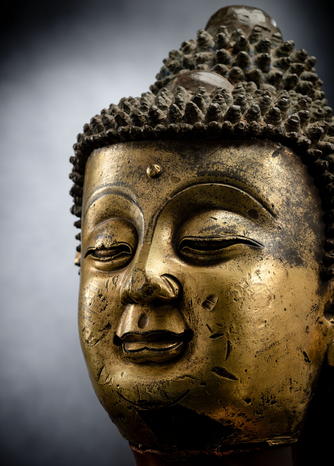 A LARGE GILT-BRONZE HEAD OF BUDDHA ON A WOOD STAND - Image 5 of 13