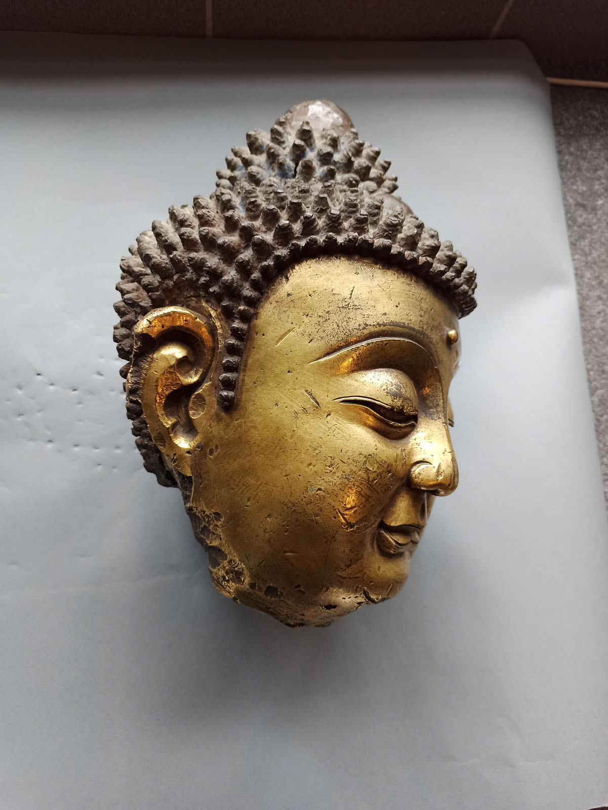 A LARGE GILT-BRONZE HEAD OF BUDDHA ON A WOOD STAND - Image 7 of 13