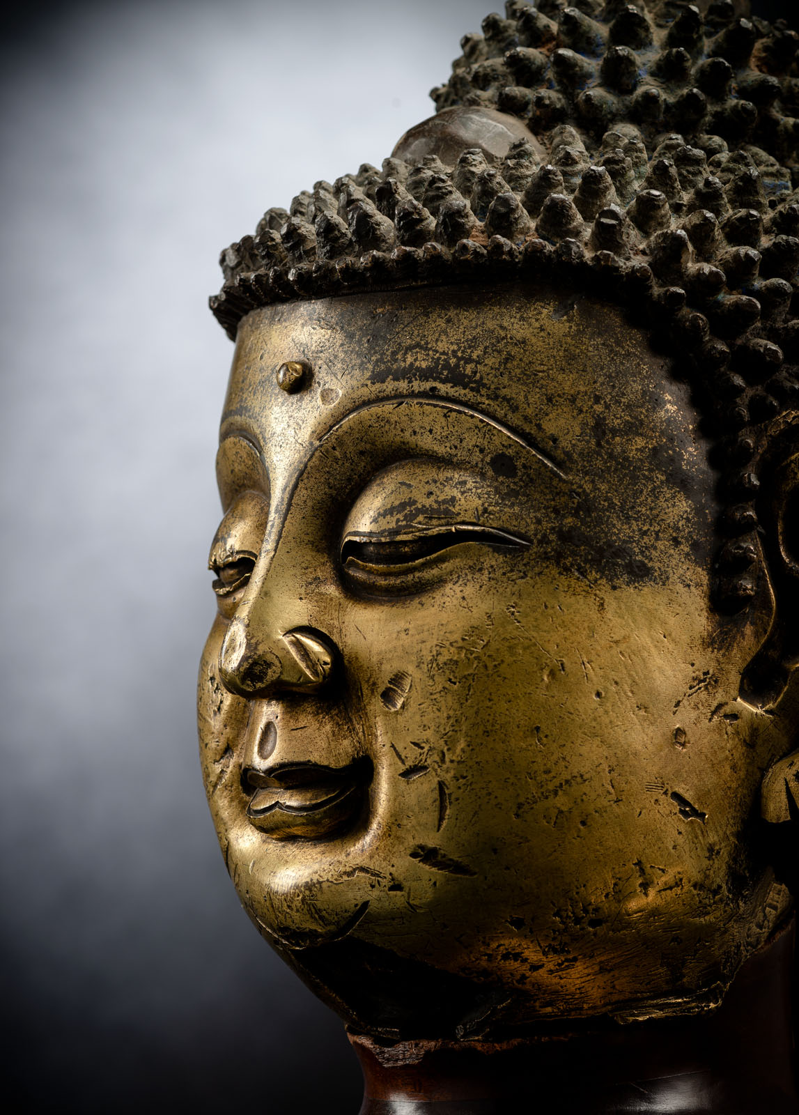 A LARGE GILT-BRONZE HEAD OF BUDDHA ON A WOOD STAND - Image 4 of 13