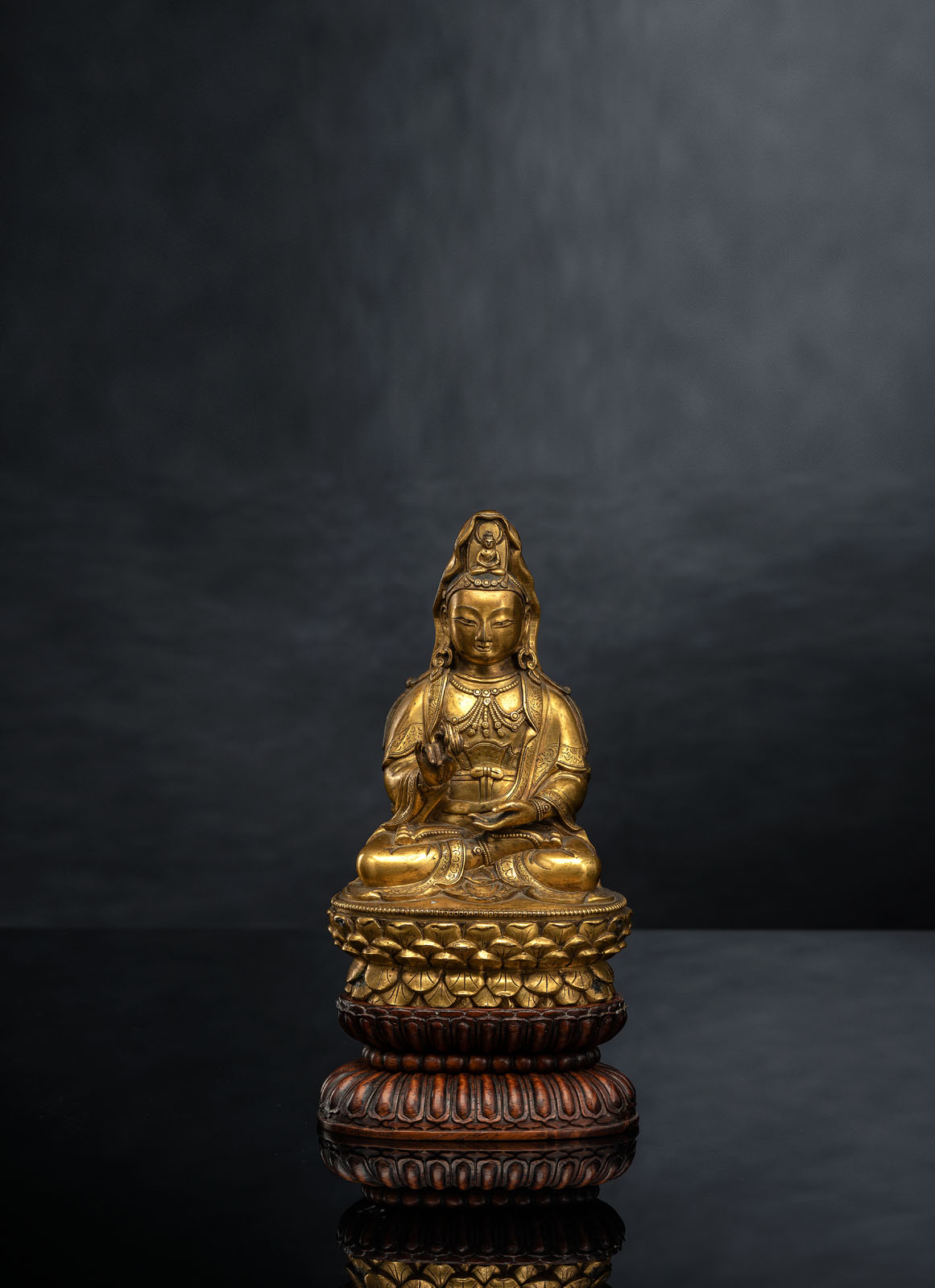 A FINE GILT-BRONZE FIGURE OF GUANYIN ON A LOTOS ABOVE A CARVED HARDWOOD LOTOS STAND