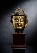 A LARGE GILT-BRONZE HEAD OF BUDDHA ON A WOOD STAND