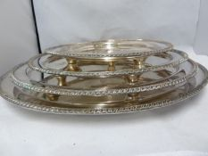 A graduated set of four silver plated salvers, circular with gadrooned edge, the centre engraved