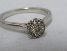 A diamond illusion 'solitaire' ring, ten small diamonds set around a central circular stone, white