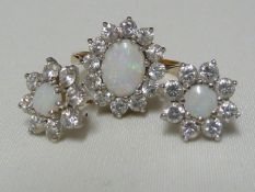 A light opal ring and earring set, the opals encircled by CZ stones, the ring of 9ct yellow gold,
