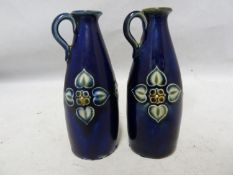 A pair of Royal Doulton stoneware miniature jugs, each with high placed strap handle and decorated
