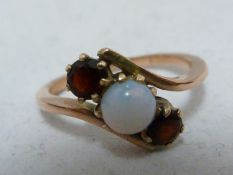 A opal and garnet ring, set in rose coloured metal, unmarked, ring size K; and two opal set
