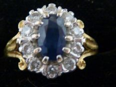A sapphire and diamond set 18ct yellow gold ring, the oval sapphire encircled by 11 diamonds, ring