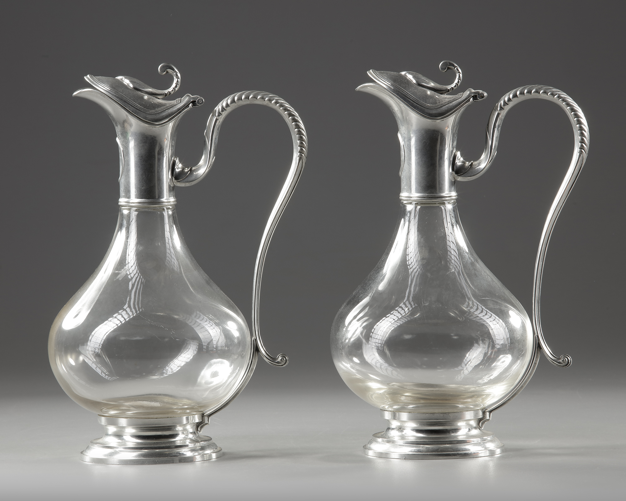 A PAIR OF CRYSTAL AND SILVER METAL EWERS, LATE 19TH CENTURY