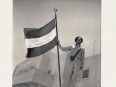 A RARE PHOTOGRAPH OF A PROUD STANDING SAUDI SOLDIER HOLDING AN UNIQUE SAUDI ARABIA FLAG, PROBABLY 19