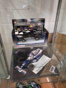 Shelf of formula one racing car models.